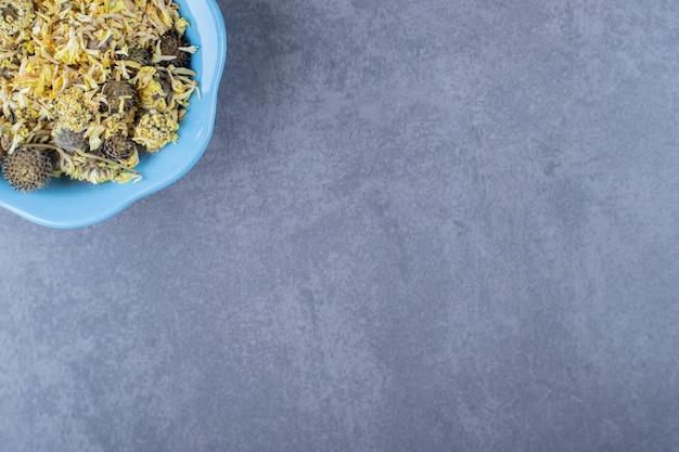 Verscheidenheid theeblaadjes in blauwe kom op grijze achtergrond.