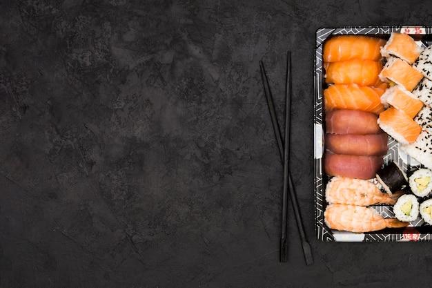 Verscheidenheid van aziatische visbroodjes op dienblad en eetstokjes over geweven achtergrond met ruimte voor tekst