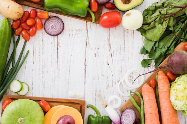 Verscheidenheid van biologische groenten op witte houten bureau