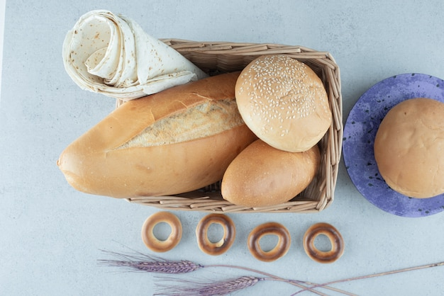 Verscheidenheid van brood in mand en crackers op stenen oppervlak