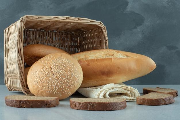 Verscheidenheid van brood in mand en tarwe op stenen tafel