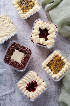 Verscheidenheid van cake in de pot voor levering. smaak van aardbei, passievrucht, chocolade en kokos. bovenaanzicht.