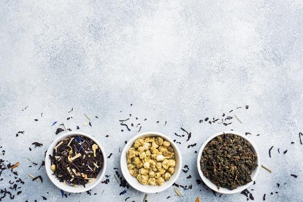 Verscheidenheid van droge theebladen en bloemen in kom op grijze achtergrond.
