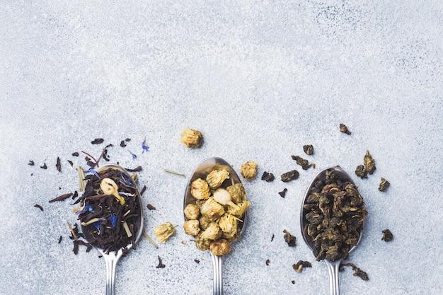 Verscheidenheid van droge theebladen en bloemen in lepels op grijze achtergrond