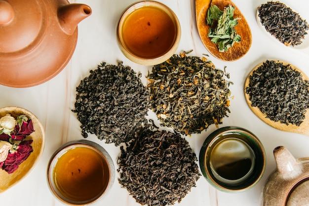 Verscheidenheid van droge theebladen en roze bloem met theekopjes en kleitheepot op geweven achtergrond