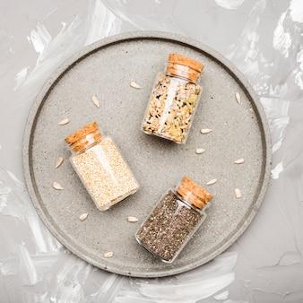 Verscheidenheid van geplette zaden in kleine glazen potten bovenaanzicht