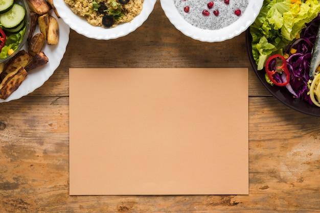 Verscheidenheid van gezond voedsel in kom met leeg pakpapier op houten lijst