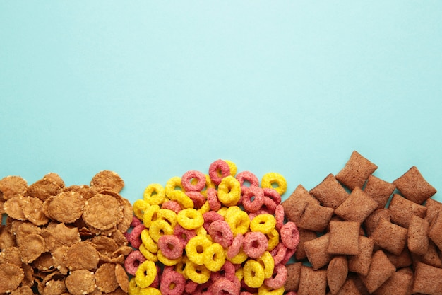Verscheidenheid van granen op blauwe achtergrond, snel ontbijt concept. bovenaanzicht