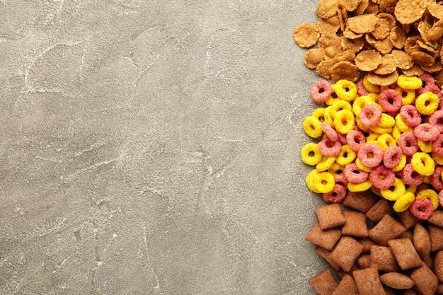 Verscheidenheid van granen op grijze achtergrond, snel ontbijt concept. bovenaanzicht