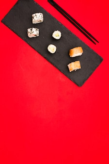 Verscheidenheid van hete die sushibroodjes op leisteen worden geschikt met eetstokjes over gekleurde achtergrond met ruimte voor tekst