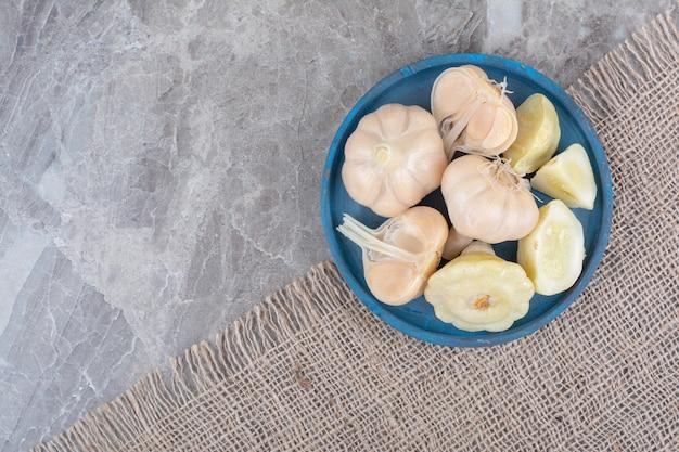 Verscheidenheid van ingemaakte groenten op blauw bord.