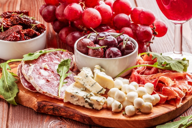 Verscheidenheid van kaas en vlees op donkere tafel.