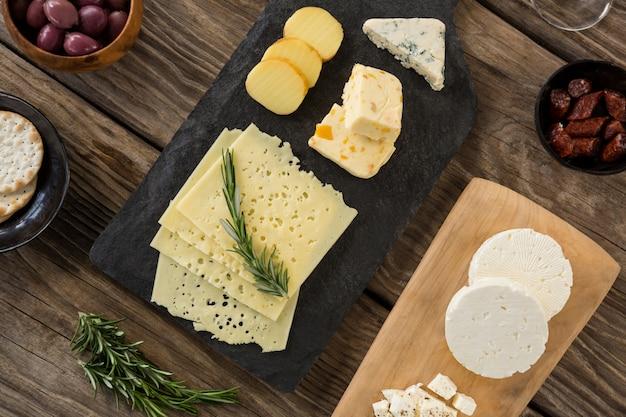 Verscheidenheid van kaas, olijven, koekjes en rozemarijn kruiden op houten tafel