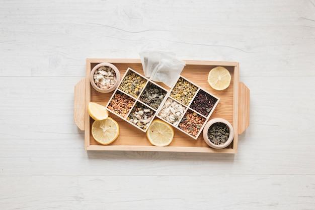Verscheidenheid van kruiden en gedroogde chinese chrysanthemum bloemen gerangschikt in kleine container op houten lade