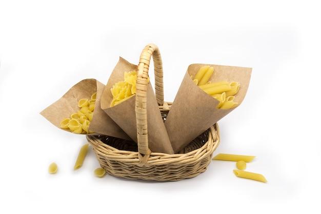 Verscheidenheid van pasta in papieren zakken in rieten mand geïsoleerd op witte achtergrond