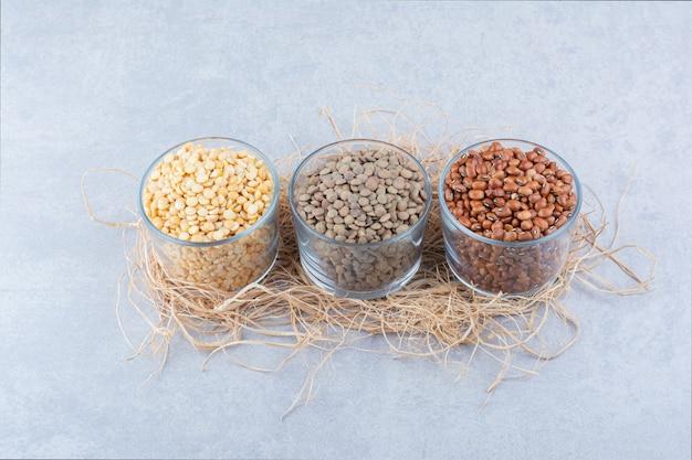 Verscheidenheid van peulvruchten geassorteerd in glazen kommen op een stapel stro op marmeren achtergrond.