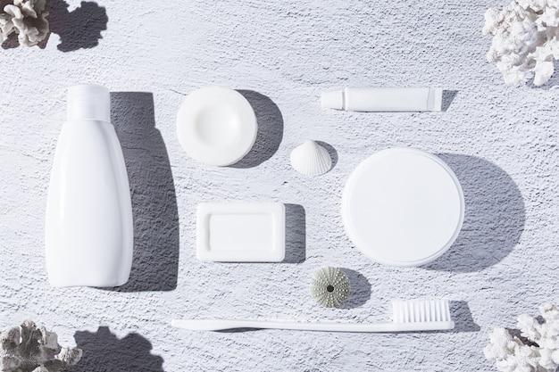 Verscheidenheid van producten voor persoonlijke hygiëne op witte achtergrond met koralen en schelpen