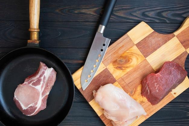 Verscheidenheid van rauw vlees rundvlees op been, varkensvlees en kipfilet op houten tafel met slager mes, bovenaanzicht