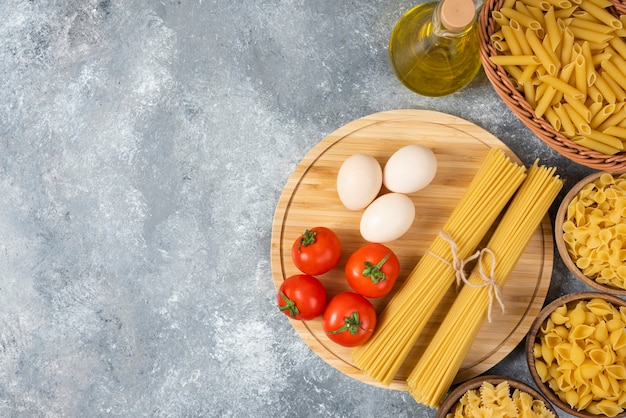 Verscheidenheid van rauwe pasta met eieren, verse tomaten en een fles olie op marmeren oppervlak.