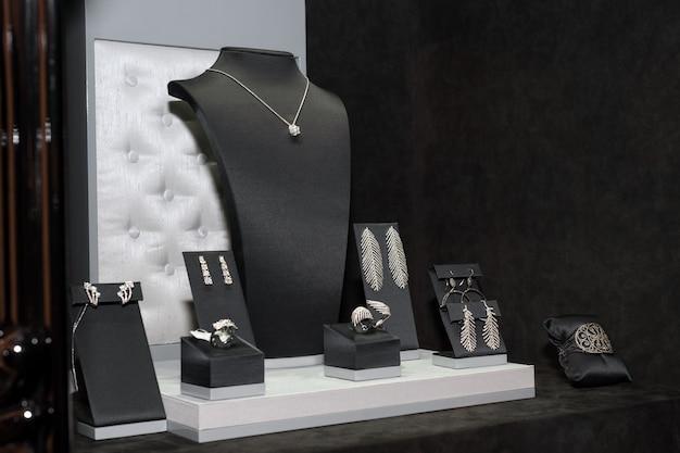 Verscheidenheid van sieraden in etalage. ringen, armbanden, oorbellen en kettingen op stands te koop.