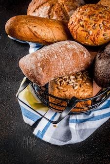 Verscheidenheid van vers zelfgemaakt graan brood, in een metalen mand, donkere roestige copyspace