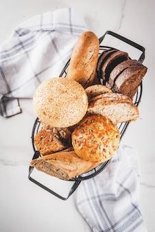 Verscheidenheid van vers zelfgemaakt graan brood, in een metalen mand, witte marmeren copyspace bovenaanzicht