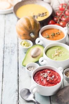 Verscheidenheid van verschillende kleurrijke groenteroomsoepen in kommen. concept van gezond eten of vegetarisch eten.