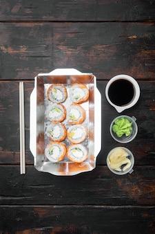 Verscheidenheid van verschillende sushi en broodjes weer, zalm en tonijn in concept set levering voedsel, op oude donkere houten tafel