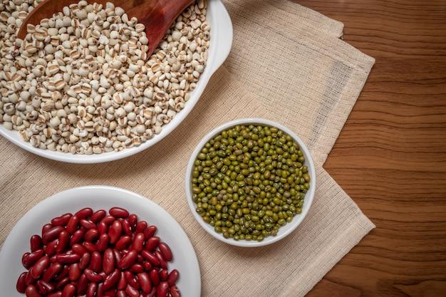 Verscheidenheid van volle granen, sperziebonen, rode bonen, gierst in een bord