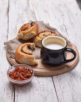 Verscheidenheid van zelfgemaakte bladerdeeg broodjes kaneel geserveerd met melk cup