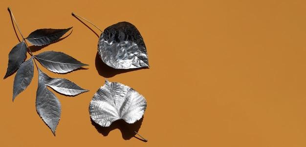 Verscheidenheid van zilver geschilderde bladeren en kopie ruimte