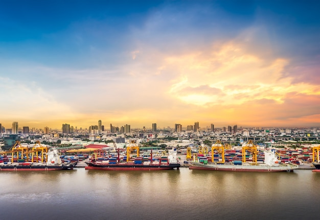 Verschepende haven met stad zonsondergang achtergrond