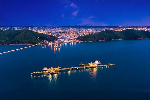 Verschepende olie en haven puntladingolie en petrochemische stof in de zee en raffinaderij fabrieksstreek met blauwe hemelachtergrond bij nacht