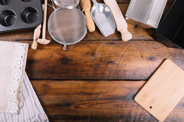 Verschillend keukenwerktuig voor het bakken van cake op houten lijst