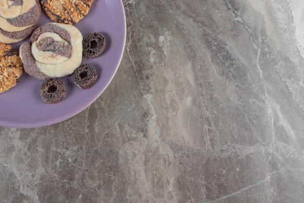 Verschillend koekjes en korenringen op een bord op marmer.
