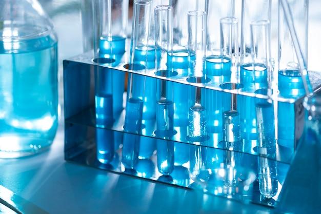 Verschillend laboratoriumglaswerk met kleurenvloeistof en met bezinning, blauwe toon
