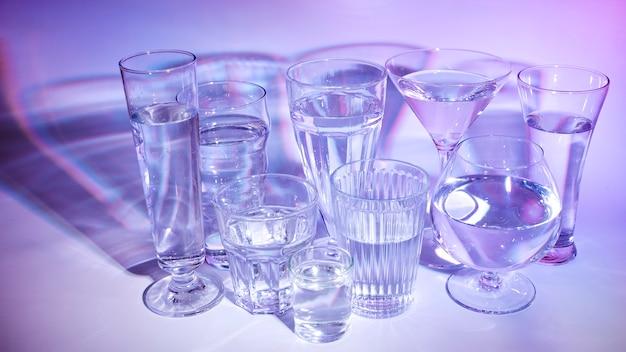 Verschillend type glazen met vloeistof op gekleurde achtergrond
