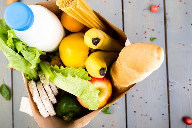 Verschillend voedsel in papieren zak op houten achtergrond
