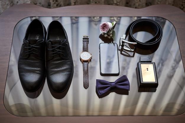 Verschillende accessoires van een zakenman voor het creëren van een stijl van een volk liggen op een houten oppervlak