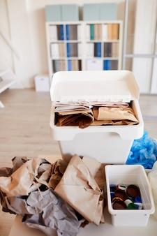 Verschillende afvalitems gesorteerd op materiaalsoort en klaar voor recycling in kantoorinterieur, focus op papierbak op voorgrond