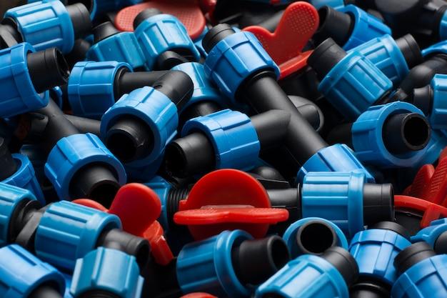 Verschillende apparatuur voor druppelirrigatie in de bouw. waterkranen, t-stukken, schakelaars en andere plastic apparatuur