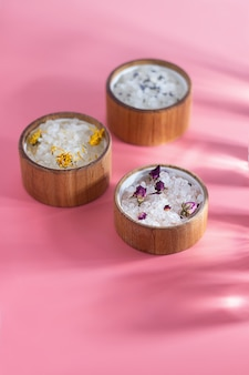 Verschillende badzout in een houten plaat op een roze achtergrond. zonnestralen. het concept van spa-behandelingen, huidverzorging. etherische oliën en gedroogde bloemen roos, lavendel.
