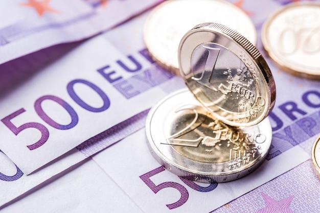 Verschillende bankbiljetten en munten van 500 euro liggen naast elkaar. symbolische foto voor wealt.euro munt balanceren op stapel met achtergrond van bankbiljetten.