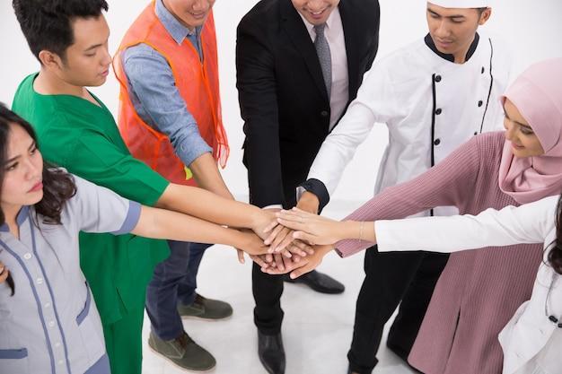 Verschillende beroepen mensen steken de handen in elkaar