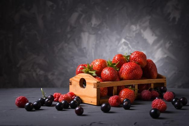 Verschillende bessen: aardbeien, kersen, frambozen, bessen in een houten mandje