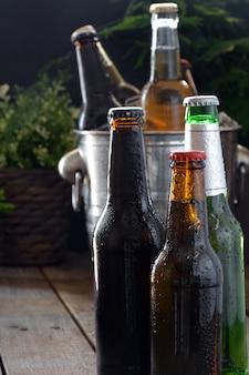 Verschillende bieren op een tafel van hout. er zijn fles en glas met ijs om ze koud te houden