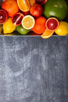 Verschillende citrusvruchten in een metaaldienblad op gray background.