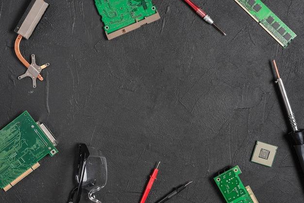 Verschillende computeronderdelen met tools op zwarte achtergrond