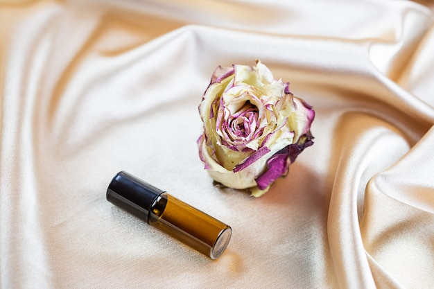 Verschillende containers voor het bewaren van cosmetica van donker glas liggen op de plooien van zijde-satijnen stof, omgeven door gedroogde rozenbloemen. parfum-, serum- of lotionfles