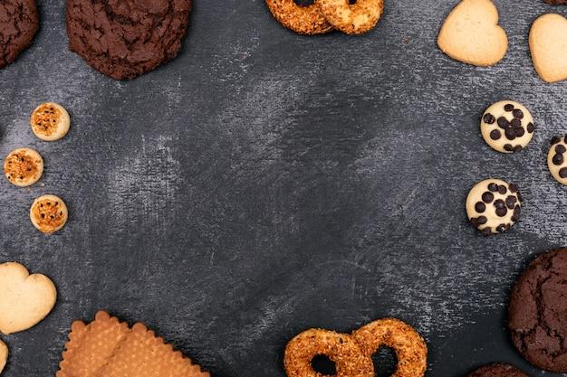 Verschillende cookies bovenaanzicht op donkere oppervlakte met kopie ruimte